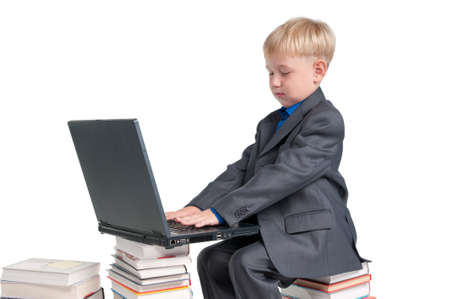 netbook: Boy studying his lessons while sitting on a pile of books Stock Photo