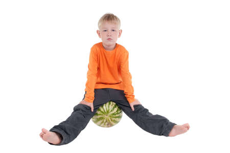8 years: Serious boy sitting on watermelon