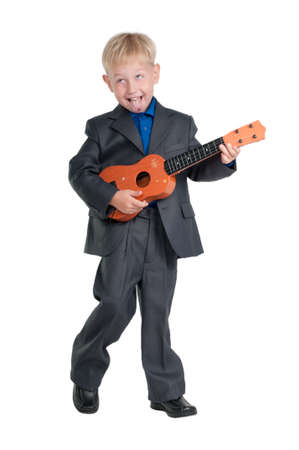 Boy in business suit having fun while playing a guitar photo