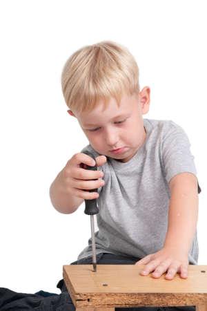 Sieben Jahre alter Junge, die mit einen Schraube-Treiber Standard-Bild