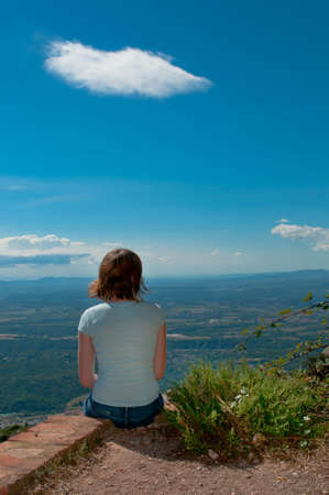 deep thought: Girl sitting on the edge and looking at the beauty of Spain. Stock Photo