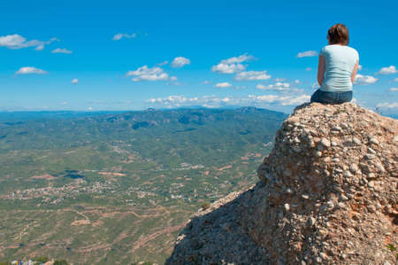 cliff edge: Young girl sitting on an edge of a cliff . Stock Photo