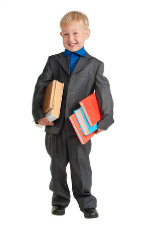 cheeky: Young smiling schoolboy holding heavy books in his arms