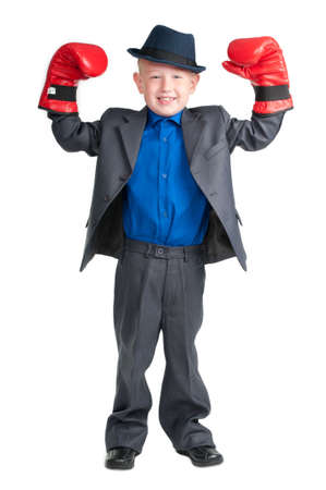 Little boy with suit and hat raising his hands in boxer gloves as winner photo