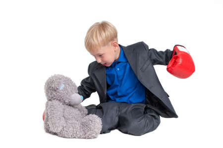 Blond boy in suit and boxer glove hitting a teddy bear