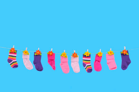 Many differently colored socks drying on a string photo