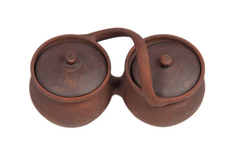 Two clay pots with lids connected together photo