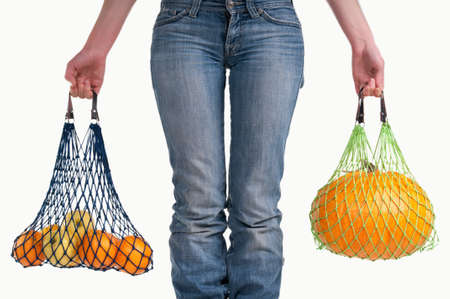 shoe strings: Woman carrying shopping bags with yellow fresh fruits isolated on white background Stock Photo