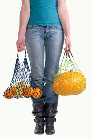 Waist-down view of young woman carrying shopping bags with yellow fruits isolated on white background Stock Photo - 8927135