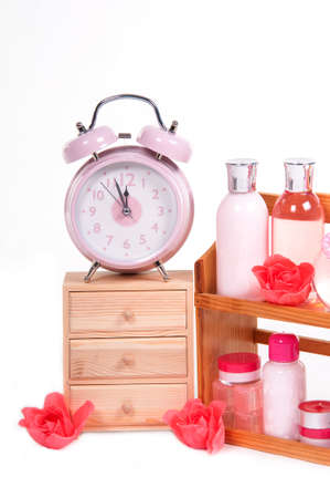 three shelves: A Cabinet with three shelves , alarm clock on top and body care accessories isolated on white background Stock Photo