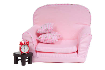 Comfortable pink armchair with a tiny table and red clock on it isolated on white background photo