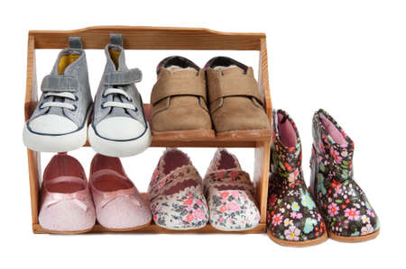 Girls different shoos for all seasons arranged on a wooden shelf isolated on white photo