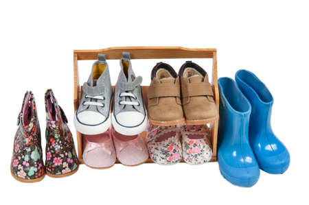 kids feet: Girls shoos for all seasons arranged on a wooden shelf isolated on white