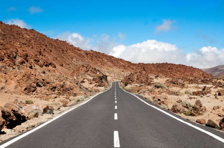 Empty road crossing an arid mountain on Lanzarote island, Canarian island, Spain in summer sunny day photo