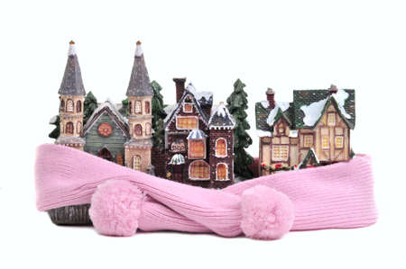 Winter toy half-timbered houses wrapped in pink scarf isolated on white background - conceptual view of protecting or isolating house photo
