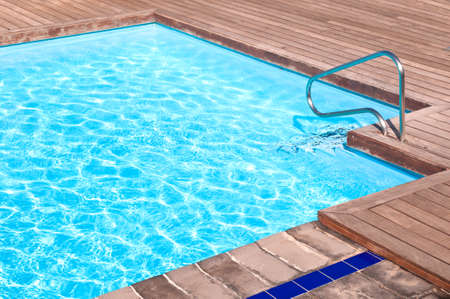 Wooden floor beside the blue swimming pool Stock Photo - 9238462
