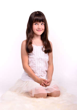 Beautiful girl in angelic costume sitting on white cloud Stock Photo - 9869948