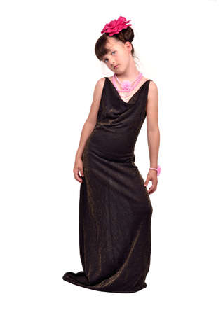 Beautiful female child wearing her mothers evening dress which is too big for her photo