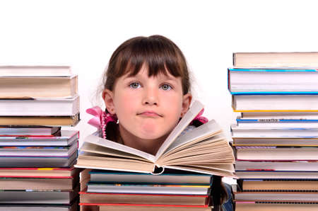 classwork: Portrait of cute girl sitting among stacks of books isolated on white background