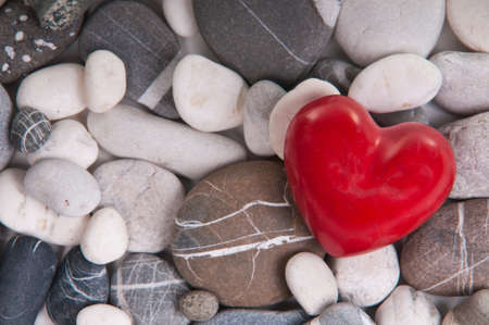 Red heart among river pebble stones photo