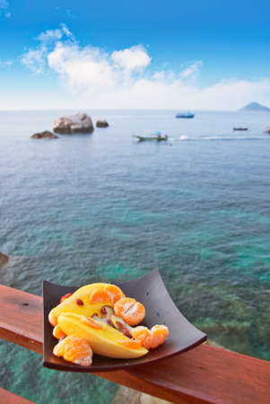 plateful: Plate full of exotic fruits on the parapet of a sea view restaurant