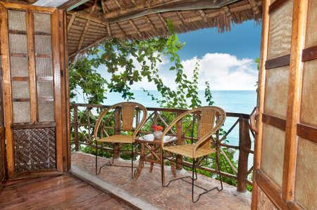 La terrasse d'un bungalow en bois avec vue sur la mer.