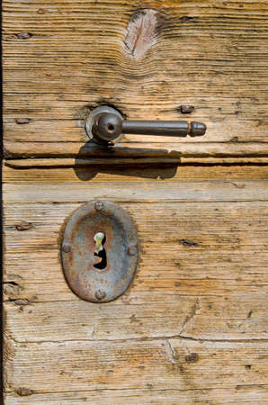 Old wooden door with rusty metal handle and key lock photo