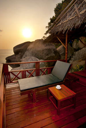veranda: Sunset sunbed on wooden terrace with coffee table Stock Photo