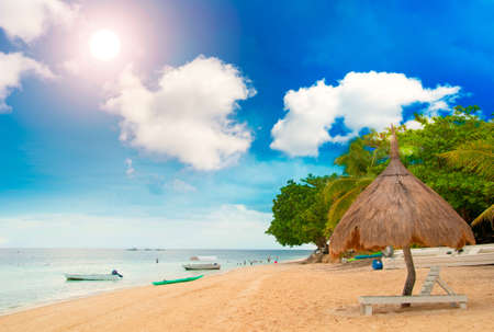 huts: Tiki Hut on the beach with sun beds Stock Photo