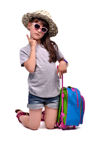Little girl with travel bag with her finger up, ready for vacation photo