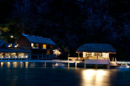 Villas of a tropical seaside resort at night, Asian island. photo