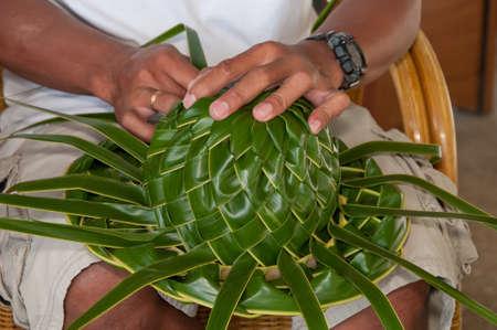 malacca: L'uomo sta facendo un cappellino in ginocchio fuori di foglie di palma.
