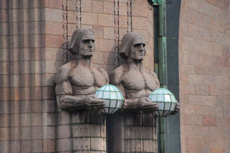 Statues at the walls of historic train station, Helsinki, Finland.