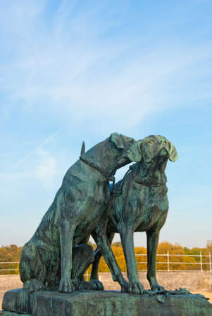 Two hunting dogs bronze statue against autumn forest background
