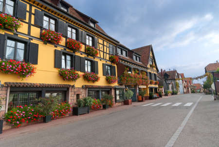 Empty street in Alsace with yellow half-timbered house with flowers.
