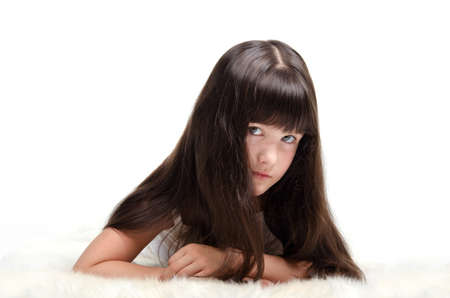Portrait of little girl with luxuriant long hair lying photo
