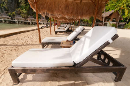 A row of beach beds with white covers under rattan huts. photo