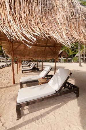Exotic Tropical Beach beds on a beach under palm hut. photo