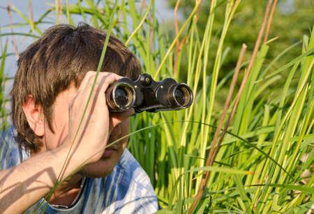 adolescentes estudiando: Hombre con binoculares tumbado en la hierba alta en la hierba