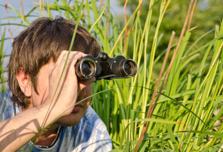 Man with binoculars lying in high grass in grass