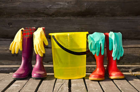 Bucket, rubber gloves and two pairs of rubber boots at sunny wooden veranda Standard-Bild