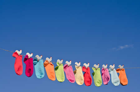 String of colorful socks on a rope against sunny blue sky in the garden  写真素材