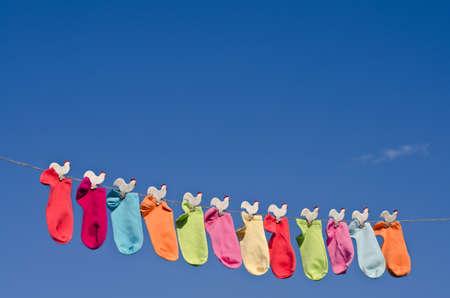 Cadena de calcetines de colores sobre una cuerda contra el cielo azul soleado en el jardín Foto de archivo