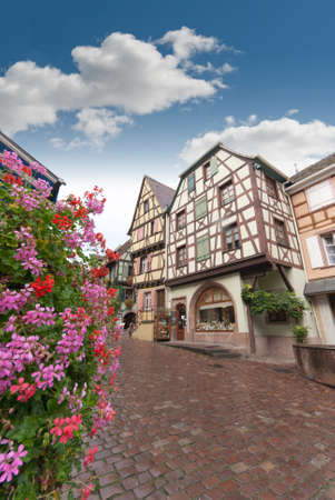 Cobbled street in Alsace with half timbered houses and flowers photo