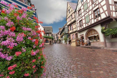 Paved street in Alsace with half-timbered houses and flowers after rain.