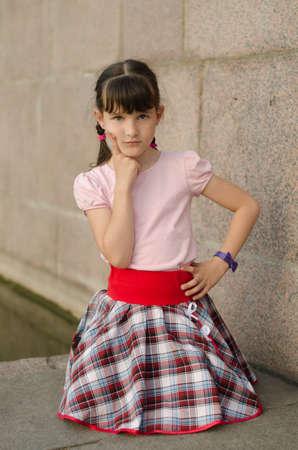 Little brunette girl sitting outdoors