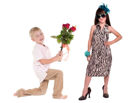 Smiling boy presenting bunch of red roses to charming girl isolated on white background photo