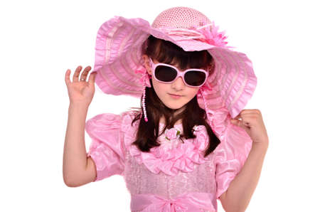 Portrait of lovely girl wearing pink dress, hat and glasses isolated on white background photo