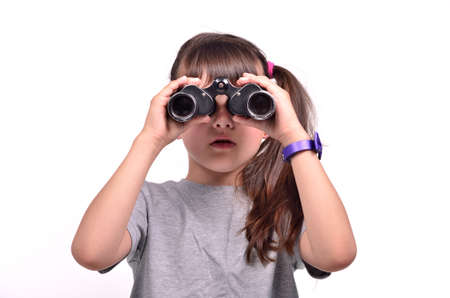 Brunette girl looking through binoculars isolated on a over white background photo