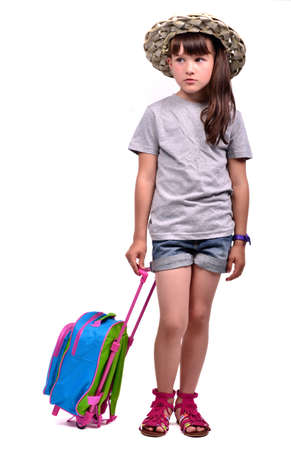 kids wear: Little girl with a travel bag over white background